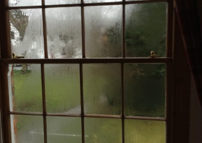Condensation on a dark wooden sash window
